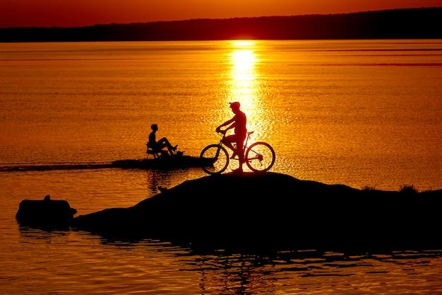 Männlicher fahrradmitfahrer steht nahe bei seinem fahrrad nahe dem fluss bei sonnenuntergang