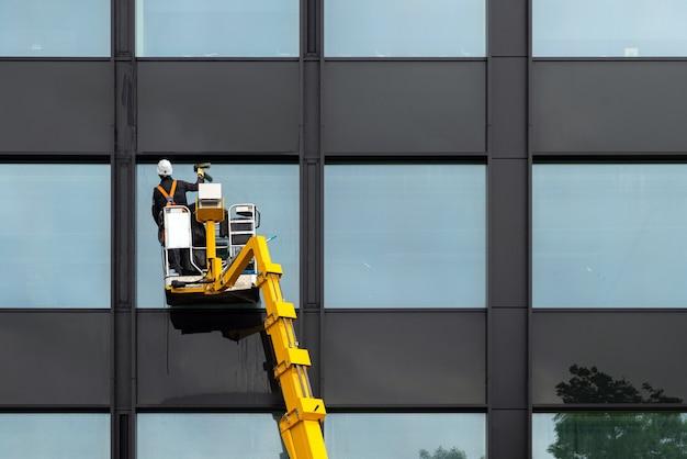 Männlicher fensterreiniger, der glasfenster auf einem modernen gebäude hoch in der luft auf einer aufzugsplattform säubert. arbeiter poliert glas hoch in der luft