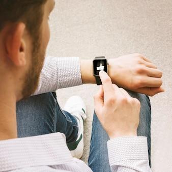 Männlicher finger klopft wie ikone auf intelligenter uhr
