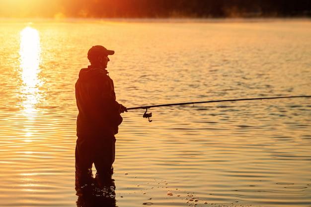 Männlicher fischer an der dämmerung auf dem see fängt eine angelrute, die hobbyferien fischt