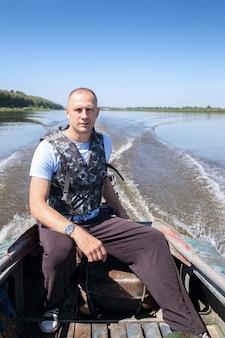 Männlicher fischer auf boot bewegt sich im fluss