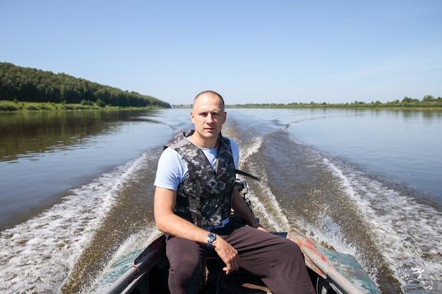 Männlicher fischer auf boot bewegt sich über einen großen fluss