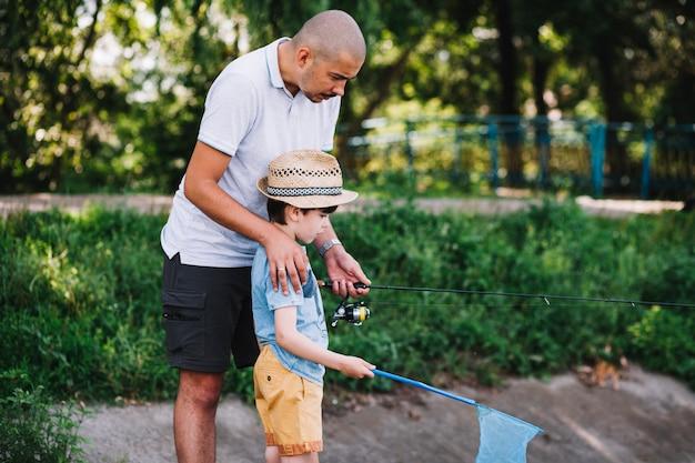 Männlicher fischer, der seinen sohn beim fischen unterstützt