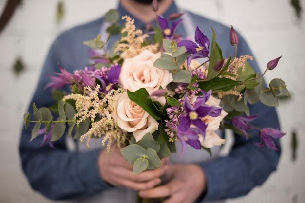 Männlicher florist defocus, der in der hand den blumenblumenstrauß hält