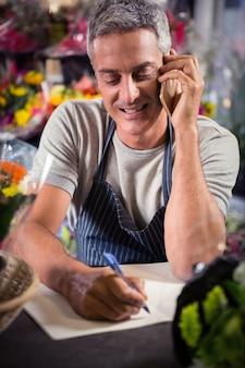 Männlicher florist, der bestellung auf handy annimmt