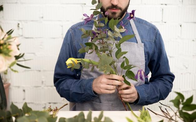 Männlicher florist, der die zweige und die blume für die herstellung des blumenstraußes vereinbart