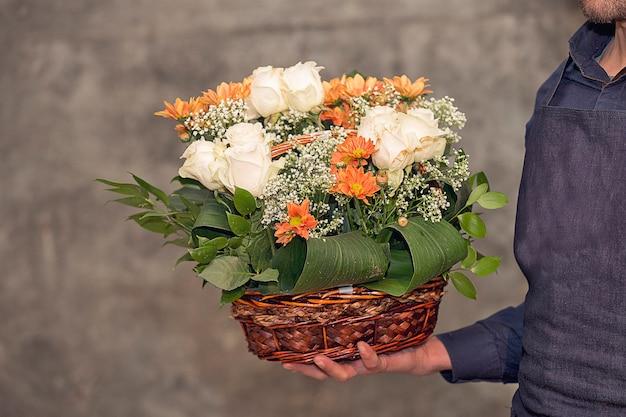 Männlicher florist, der einen blumenblumenstrauß innerhalb des korbes fördert.