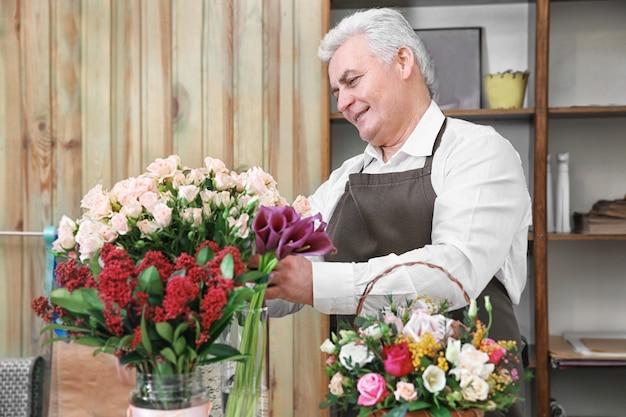 Männlicher florist, der sich um blumen im blumenladen kümmert