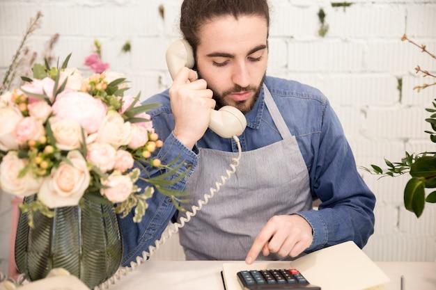 Männlicher florist, der taschenrechner bei der unterhaltung am telefon verwendet
