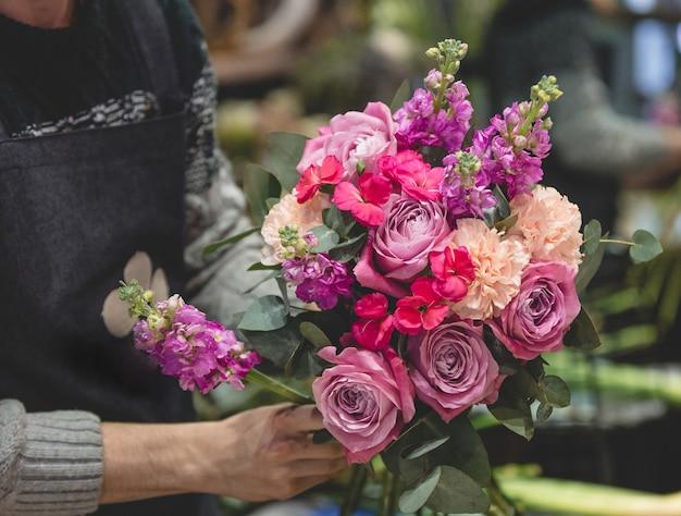 Männlicher florist makinf ein bunter blumenblumenstrauß