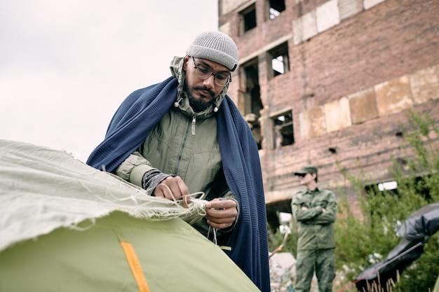 Männlicher flüchtling, der zelt gegen halb zerstörtes gebäude aufschlägt