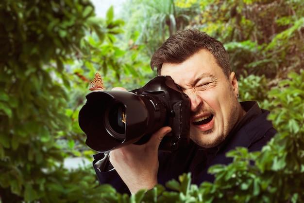 Männlicher fotograf bei der arbeit, schöner schmetterling, der auf der kameralinse, grüner wald sitzt