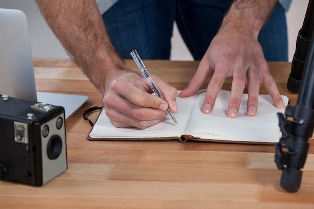 Männlicher fotograf, der am schreibtisch arbeitet