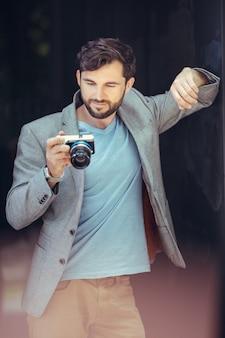 Männlicher fotograf, der auf bildschirm von vorne schaut