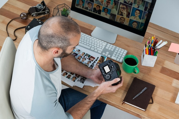Männlicher fotograf, der aufgenommene fotos in seiner digitalkamera überprüft