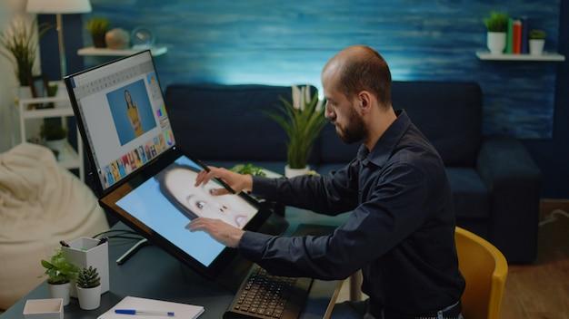 Männlicher fotograf, der bearbeitungsarbeiten auf dem touchscreen erledigt