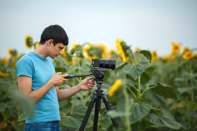 Männlicher fotograf, der bilder in einem feld von sonnenblumen macht
