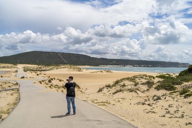 Männlicher fotograf, der durch einen strand unter einem bewölkten himmel am tag in andalusien, spanien geht
