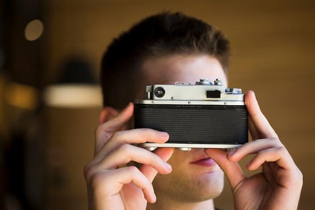 Männlicher fotograf, der foto mit weinlesekamera macht