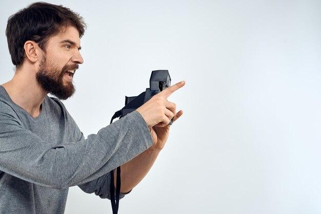 Männlicher fotograf, der kamera isoliert hält