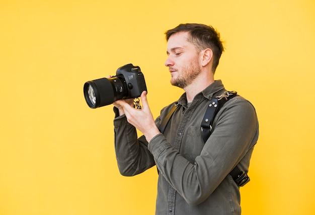 Männlicher fotograf, der kameraschirm betrachtet