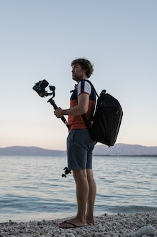 Männlicher fotograf, der seine kamera auf kardanstab hält