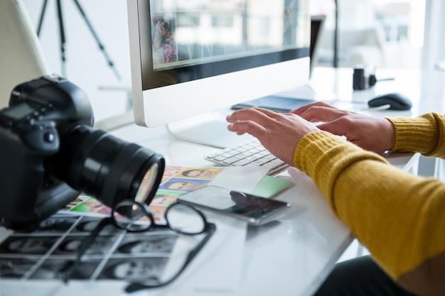 Männlicher fotograf, der über computer am schreibtisch arbeitet