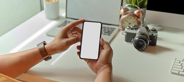 Männlicher fotograf, der verspottetes smartphone hält, während er am schreibtisch mit büromaterial sitzt