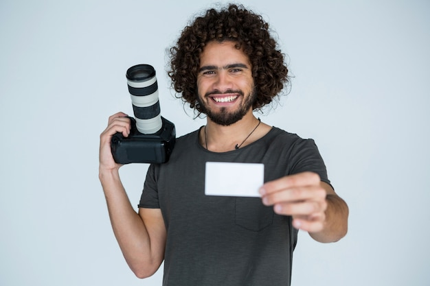 Männlicher fotograf, der visitenkarte im studio zeigt