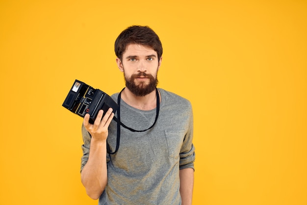 Männlicher fotograf mit professioneller fotokamera. professioneller kreativer ansatz studio gelber hintergrund. hochwertiges foto