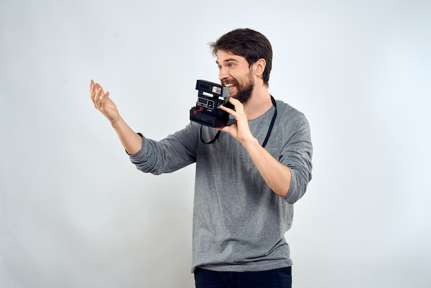 Männlicher fotograf professionelle kameraarbeit studio technologie moderne kunst hellen hintergrund. hochwertiges foto