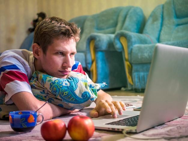 Männlicher freiberufler, der zu hause vor dem arbeiten des laptops liegt