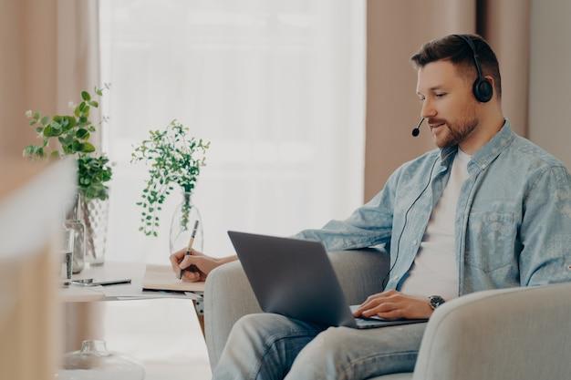 Männlicher freiberufler hört aufmerksam zu tutorials, wie man ein eigenes unternehmen gründet schreibt informationen auf trägt stereo-kopfhörer und laptop arbeitet online von zu hause aus macht videoanrufe sieht webinar