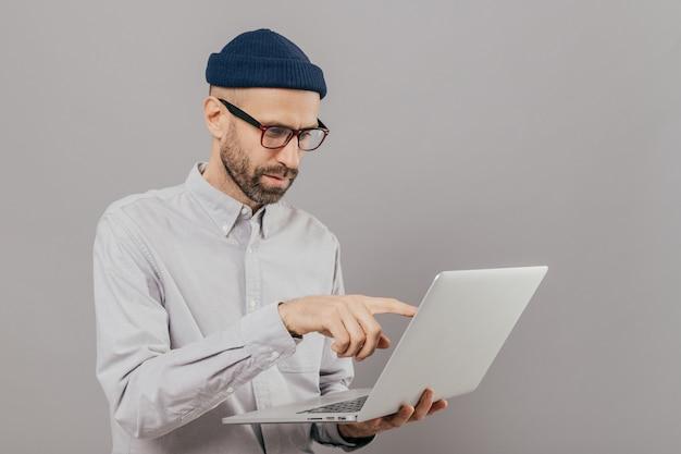 Männlicher freiberufler lässt projekt, punkte mit dem zeigefinger am schirm der laptop-computers arbeiten