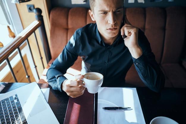 Männlicher freiberuflicher geschäftsmann-geschäftsmann, der im café arbeitet
