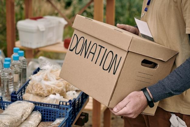 Männlicher freiwilliger, der eine gepackte spendenbox hält