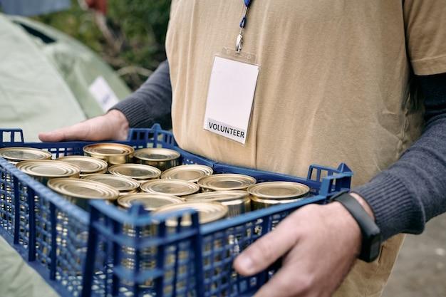 Männlicher freiwilliger, der eine plastikbox mit konserven trägt
