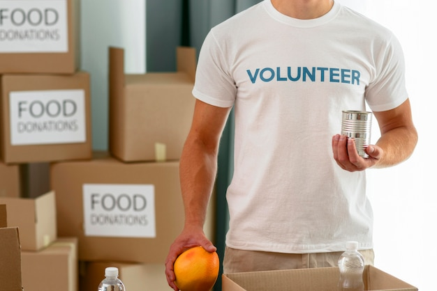 Männlicher freiwilliger, der essen vorbereitet, um für wohltätige zwecke zu spenden