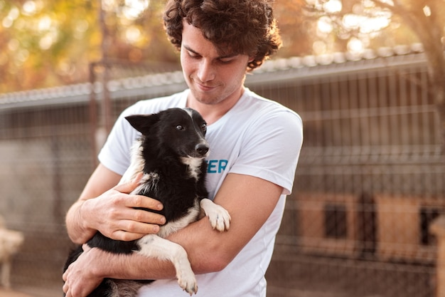 Männlicher freiwilliger, der hund im schutz umarmt