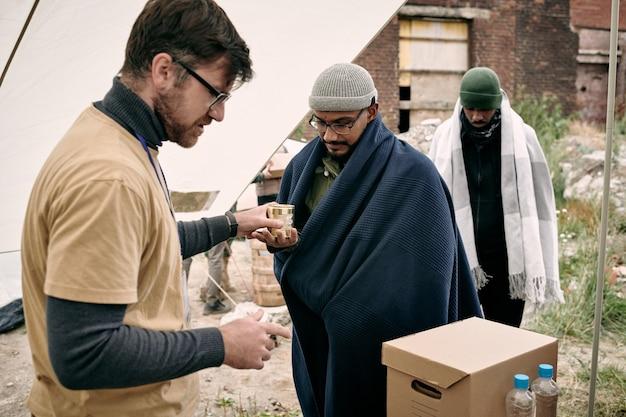 Männlicher freiwilliger, der migranten humanitäre hilfe leistet