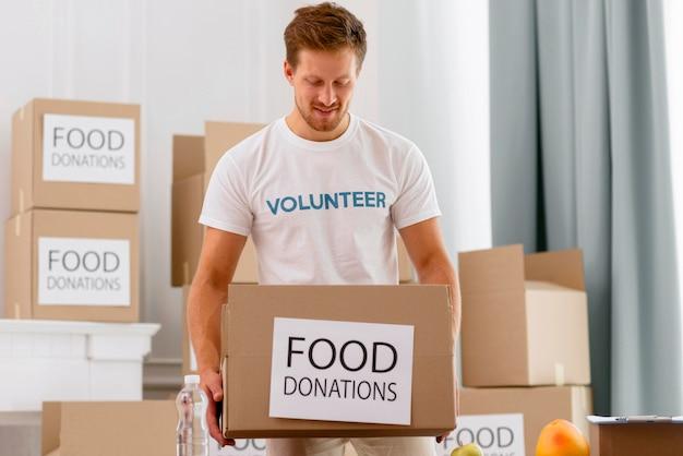 Männlicher freiwilliger, der mit kisten mit spenden arbeitet