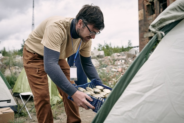 Männlicher freiwilliger mit einer schachtel mit konserven, die sich im zelt verbiegen