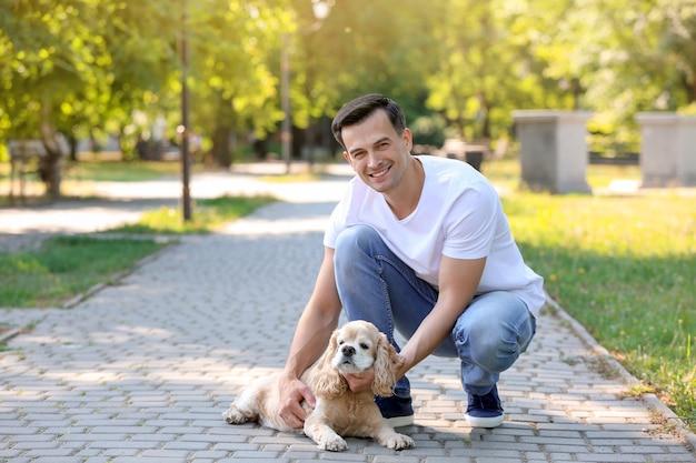 Männlicher freiwilliger mit niedlichem hund im freien