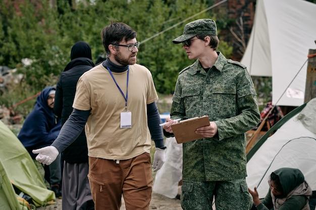 Männlicher freiwilliger und junger mann in grüner uniform diskutieren arbeitspunkte