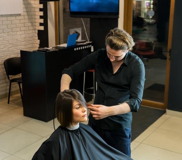 Männlicher friseur bereitet sich auf den haarschnitt der schönen frau im schönheitssalon vor.