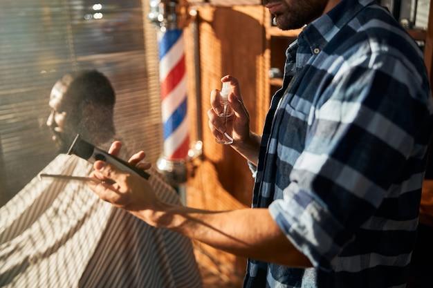 Männlicher friseur, der friseurwerkzeuge vor dem haarschnitt desinfiziert