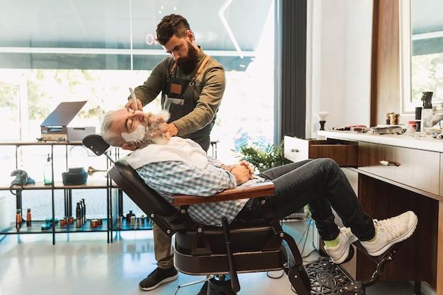Männlicher friseur, der für das rasieren des älteren kunden im friseursalon sich vorbereitet