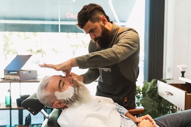 Männlicher friseur, der für das rasieren des älteren kunden sich vorbereitet