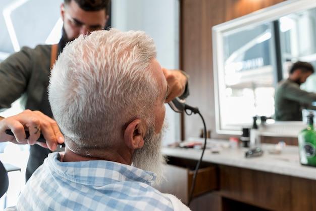 Männlicher friseur, der haar des älteren kunden trimmt