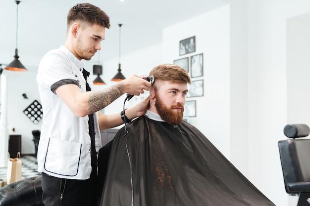 Männlicher friseur, der haare mit elektrorasierer im friseursalon schneidet